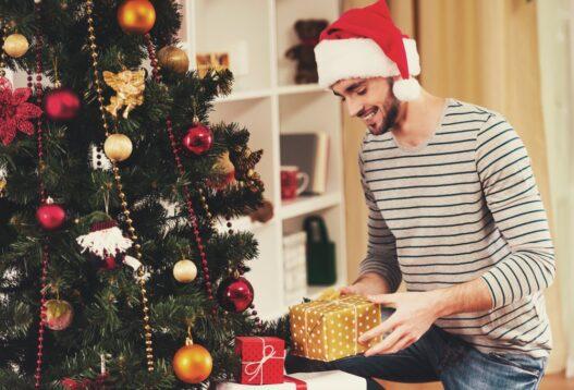 Mand med julegaver ved juletræet